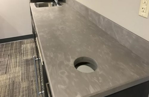 Long Gray Counter Top With Sink and Trash Enclosure