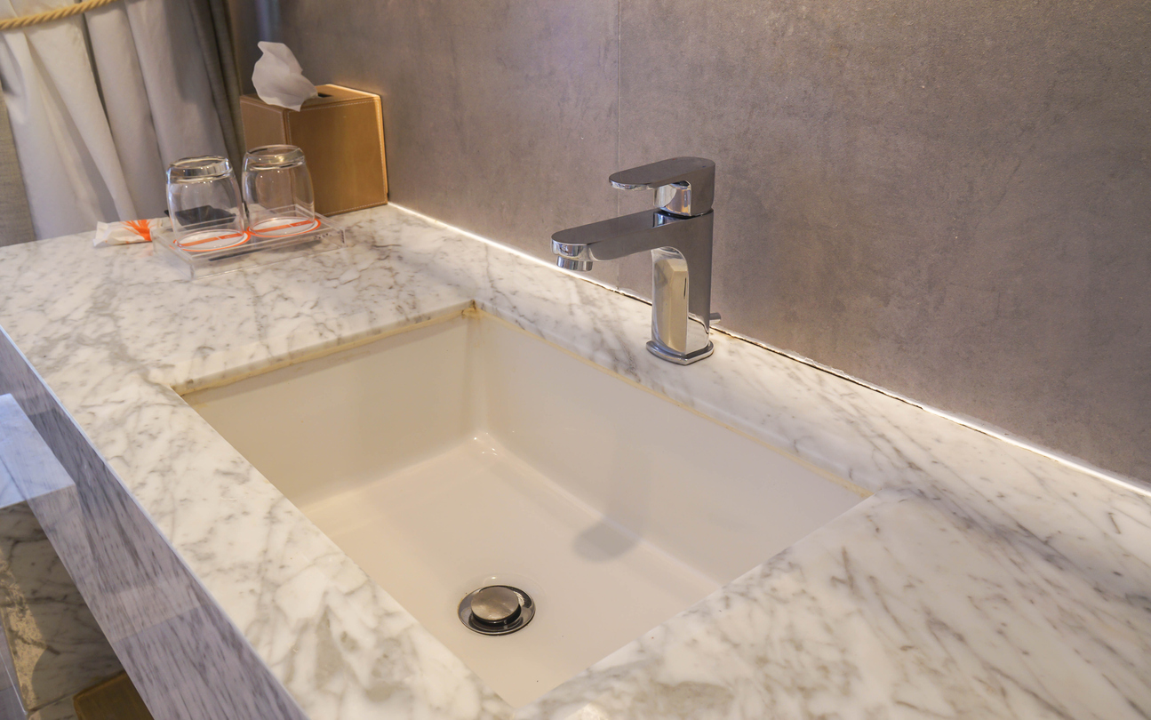 Faucet and Luxury Marble Washbasin In Hotel Bathroom